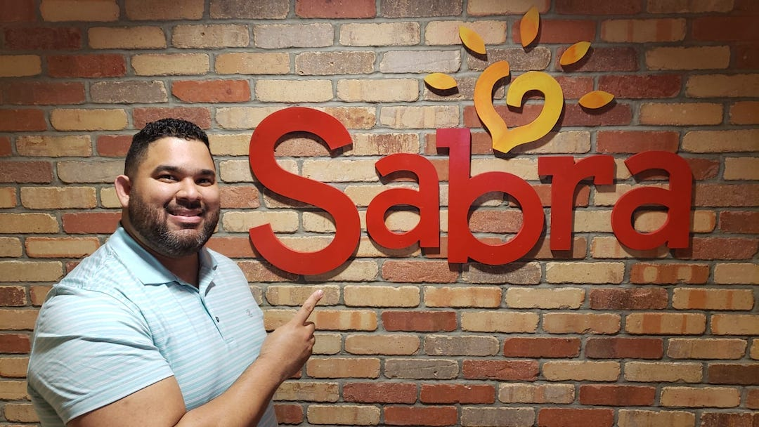 Juan Vargas, PMP, in front of a Sabra sign on the company's corporate offices.