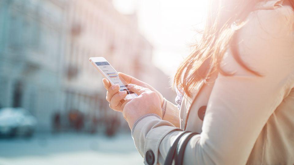 A woman uses a smartphone on a city sidewalk.